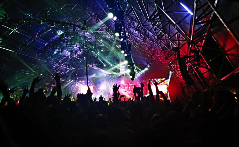 A view of the stage, roof and lights over the crowd at a Trance music festival